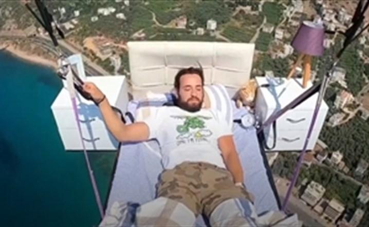 رجل يمارس الطيران المظلي و هو في سريره